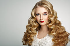 Fashion portrait of young beautiful woman with elegant hairstyle. Beautiful girl with long wavy and shiny hair . Blonde woman with curly hairstyle. Perfect make Royalty Free Stock Photos