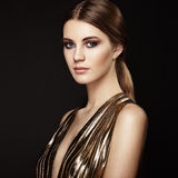 Fashion portrait of young beautiful woman in gold dress Royalty Free Stock Image