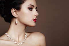 Fashion portrait of young beautiful woman with jewelry. Brunette girl. Perfect make-up. Beauty style woman with diamond accessories royalty free stock photography