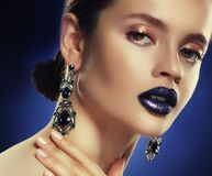 Fashion portrait of young beautiful woman with jewelry. Perfect make-up. Blue lips. Stock Photos
