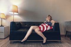 Fashion model laying down on sofa Royalty Free Stock Images