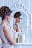 Fashion portrait of young beautiful woman looking in antique mir Royalty Free Stock Photos