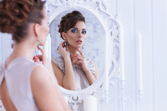 Fashion portrait of young beautiful woman looking in antique mir Royalty Free Stock Image