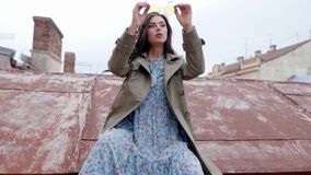 Fashion portrait of young beautiful woman posing on the roof. Stylish girl sitting in the old part of the town against