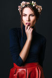 Fashion portrait of young beautiful woman in skirt and shirt. Black background Stock Image