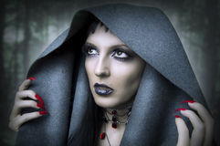 Fashion portrait of young beauty woman. Witch in dark forest. Makeup and style for halloween royalty free stock photo