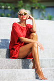 Fashion portrait of young beauty woman in red dress posing outdo stock photography