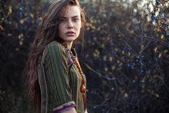 Fashion portrait of young boho girl at sunset posing on nature royalty free stock photography