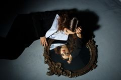 Performance with a girl and mirror. Fashion portrait of young brunette with hairstyle, red lips Royalty Free Stock Photography