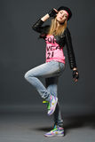 Fashion portrait of young casual girl. Fashion portrait of young gloved girl wearing on hat, leather jacket, blue jeans and pink t-shirt and bright sneakers Royalty Free Stock Images