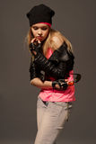 Fashion portrait of young casual girl. Fashion portrait of young gloved girl wearing on hat, leather jacket, blue jeans and pink t-shirt Royalty Free Stock Photo