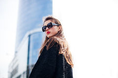Fashion portrait of young elegant confident woman outdoor. black jacket, red lips and sunglasses. On the background of the big city Stock Images