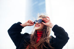 Fashion portrait of young elegant confident woman outdoor. black jacket, red lips and sunglasses. On the background of the big city.hipster having fun and Stock Photo