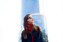 Fashion portrait of young elegant confident woman outdoor. black jacket, red lips and sunglasses. She looking at the sky. On the background of the big city Stock Images