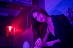 Fashion portrait of young elegant girl. Beautiful brunette woman in neon light. Underwear, jacket shows a bare tummy. Colored royalty free stock photo