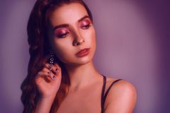 Fashion portrait of young elegant girl in jewelry. Colored background, studio shot. Beautiful brunette woman. Girl posing in neon. Light. Woman with stylish stock images