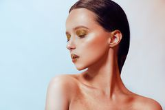 Fashion portrait of young elegant girl. Paslet background, studio shot. Beautiful brunette woman with gold lips and golden bright stock photo
