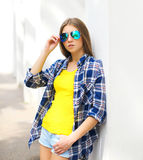 Fashion portrait young girl wearing a sunglasses and checkered shirt Stock Photo