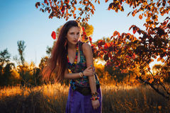 Fashion portrait of young hippie woman walking in autumn field. Romantic sunny evening.  Royalty Free Stock Photo