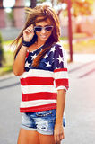 Fashion portrait of young hipster woman wearing sunglasses at sunset, american style. Outdoor stock images