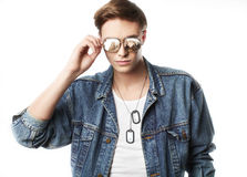 Fashion portrait of the young  man. Wearing jeans jaket with reflection in glasess Stock Photography