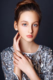 Fashion portrait. young model wearing silver evening dress. Studio black background . Stock Photos