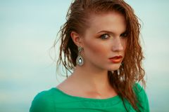 Fashion portrait of young model with wet long ginger red hair royalty free stock images