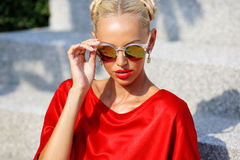Fashion portrait of young pretty blonde girl in red dress and su Stock Images