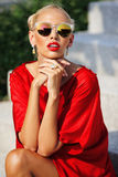 Fashion portrait of young pretty blonde girl in red dress and su Stock Photography