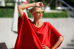 Fashion portrait of young pretty blonde girl in red dress and su Royalty Free Stock Images