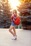 Fashion portrait of young pretty hipster woman outdoor with long hair and red backpack in the sunny summer street. The royalty free stock photos