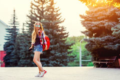 Fashion portrait of young pretty hipster woman outdoor with long hair and red backpack in the sunny summer street. The royalty free stock photo