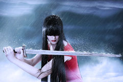 Fashion portrait of young pretty woman fighter. Fashion fantasy portrait of young pretty brunette woman fighter with sword in mist royalty free stock images