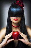 Fashion portrait of young sexy female model. Glamour brunette woman with long black healthy hair and beautiful red lips and fresh apple Royalty Free Stock Photo