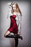 Fashion portrait of young sexy woman. In red dress, gray leather jackets and black long boots on high heel Royalty Free Stock Photography