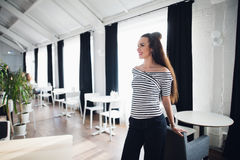 Fashion portrait of young smiling woman standing near the table in modern cafe. Beautiful adult brunette woman relaxing Royalty Free Stock Photography