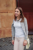 Fashion portrait of young trendy woman walking. Closeup of young trendy woman wearing gray jacket, pink jeans and white satchel bag walking on the street Stock Photos