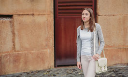 Fashion portrait of young trendy woman walking. Closeup of young trendy woman wearing gray jacket, pink jeans and white satchel bag walking on the street Royalty Free Stock Images