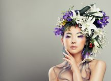 Fashion Portrait of Young Woman with Beautiful Flowers. Hairstyle and Fashion Makeup. Fashion Girl with White Lily and Iris Flowers Stock Photos