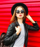 Fashion portrait young woman in black rock style stands over red Royalty Free Stock Photos