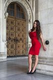 Fashion portrait of a young woman with curly hair wearing red dress Royalty Free Stock Photos