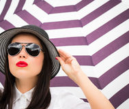 Fashion portrait of a young woman in a hat and sunglasses Stock Photos