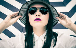 Fashion portrait of a young woman in a hat and sunglasses Royalty Free Stock Images