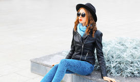 Fashion portrait young woman model wearing a black rock jacket hat in city Stock Photos
