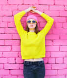 Fashion portrait young woman posing over colorful pink brick. Background stock images