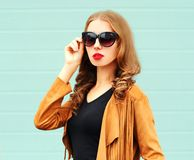 Fashion portrait young woman posing in sunglasses on wall stock images