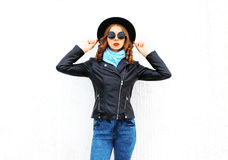 Fashion portrait young woman posing wearing a black jacket over white. Background Royalty Free Stock Images