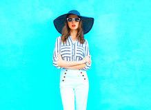 Fashion portrait young woman is posing wearing a straw in the city over colorful blue Royalty Free Stock Photos