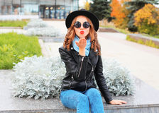 Fashion portrait young woman sends air kiss blowing red lips wearing black hat in city Stock Photography