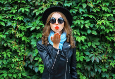 Fashion portrait young woman sends air kiss blowing red lips wearing a black hat over green leaves. Background royalty free stock photography